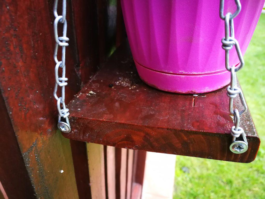 În lateralul suporților pentru jardiniere sunt prinse cu suruburi bucăți de lanț decorativ