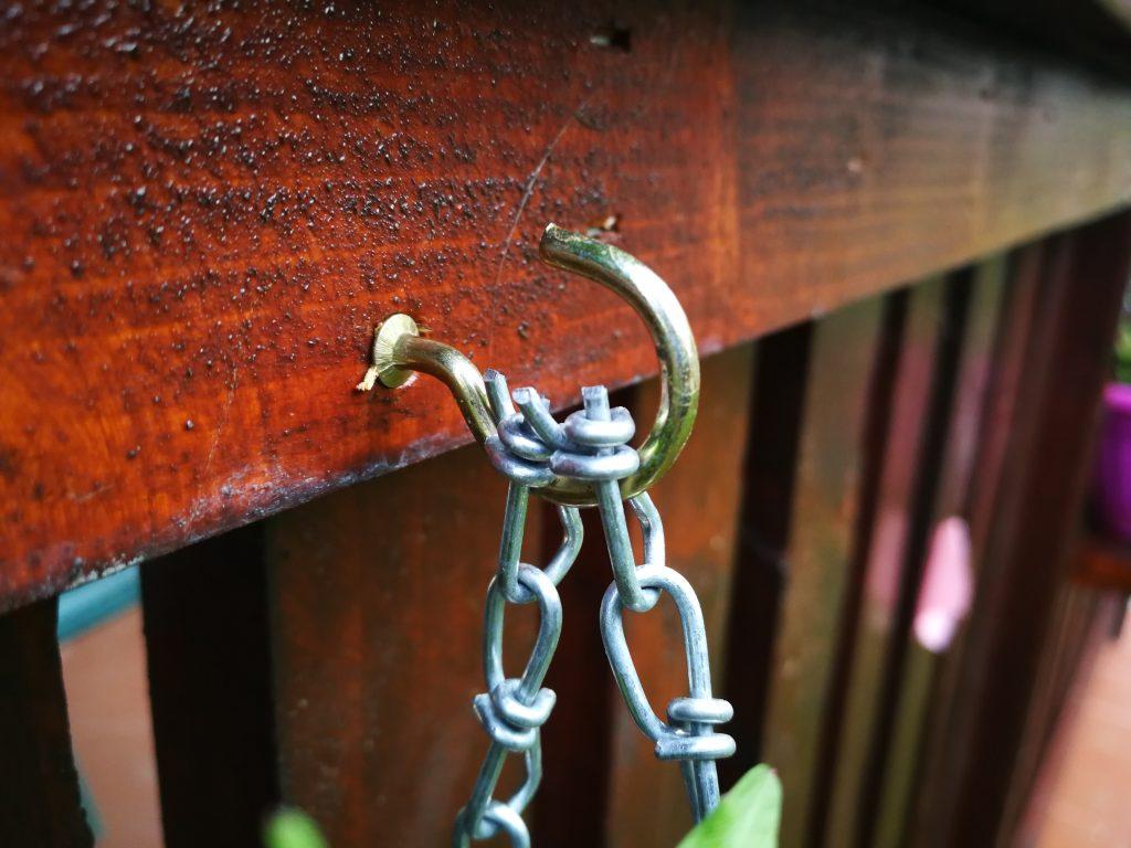 Cârlig cu capăt filetant fixat în scândură, prin care sunt trecute capetele lanțurilor decorative ce sunțin suporții de jardiniere