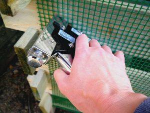 Pistol cu capse folosit pentru prinderea rețelei de plastic pe lada pentru compost