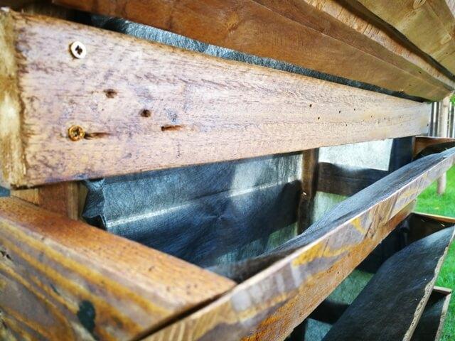 Detaliul unei construcții din lemn tapetată cu pânză antiburuieni