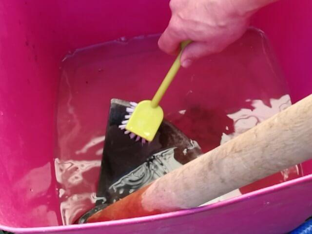 Spălare sapă cu peria într-un recipient din plastic