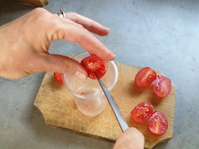 Semințele de roșii pentru răsaduri sunt scoase cu cuțitul și puse într-un pahar