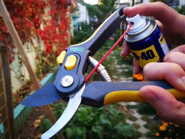 Gresarea mecanismului unei foarfeci de grădină cu un produs dintr-un tub sub presiune